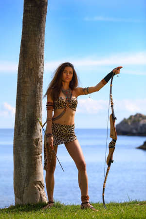 Attractive Amazon girl with bow a bow and arrows on a background of sea and blue sky Archivio Fotografico