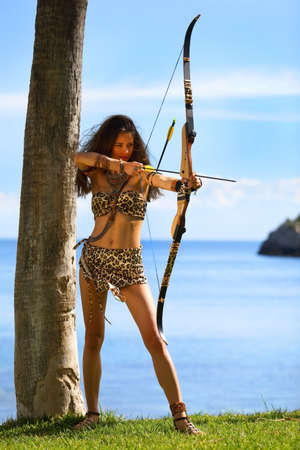 Beautiful young Amazon aims a bow at the target outdoors