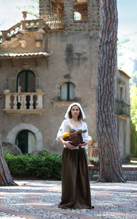 Une jeune jolie paysanne avec un panier de légumes marche dans la rue dans le contexte d'un vieux manoir Banque d'images