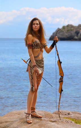 Hermosa joven en un traje de Amazon con un arco y flechas sobre un fondo de cielo azul y mar Foto de archivo