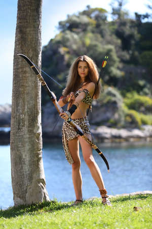 Young pretty savage with a bow and arrows on a background of sea and blue sky