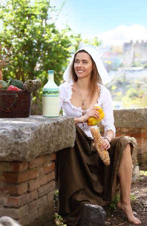 Joven campesina se sentó a hacer un picnic. En la mesa junto a su canasta de comida y una botella de leche.