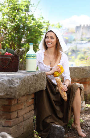 Young peasant girl sat down for a picnic. On the table next to her basket of food and a bottle of milk