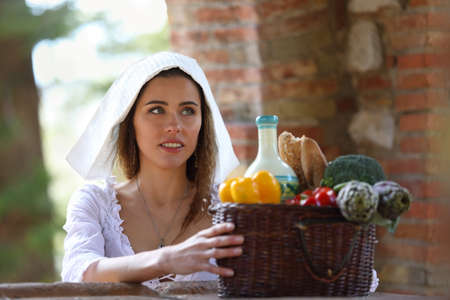 A young pretty peasant woman with a basket of products sat down to relax in the courtyard
