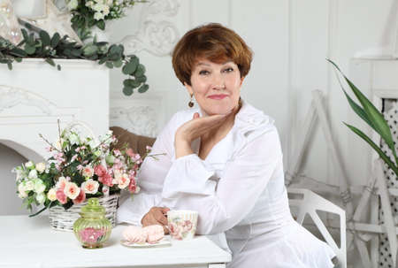 Portrait of an attractive middle aged woman sitting at a table with flowers in the living room bathed in light