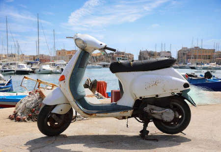 Old Italian scooter on the city pier in Syracuse city. Sicily, Italy