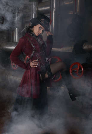 Pretty young steampunk woman shrouded in steam over industrial background with pipes and valves