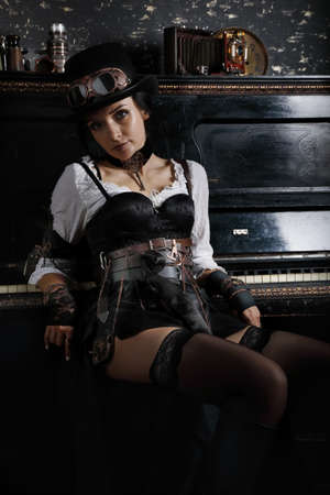 Cute steampunk woman sits next to the piano in a vintage interior