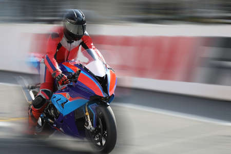 Motorcycle rider in helmet racing at high speed on race track with motion blur