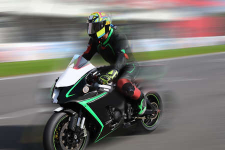 Racer on a sports bike rides on the race track at high speed with motion blur 스톡 콘텐츠