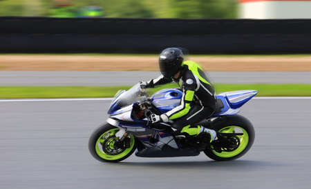 Racing bike rider in helmet racing at high speed on race track with motion blur