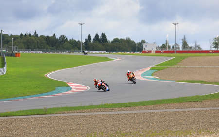 Two motorcycle racers compete on the race track Imagens