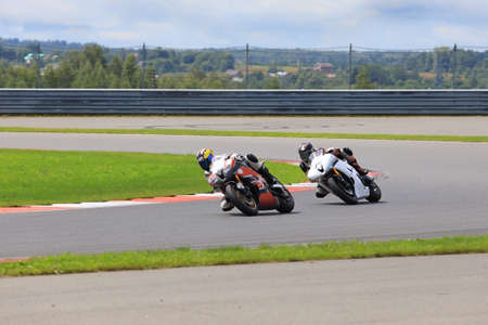 Two riders on motorcycles riding on the race track at high speed