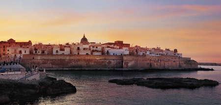Sunset panorama of Monopoli harbor in the Metropolitan City of Bari and region of Apulia (Puglia), Italy