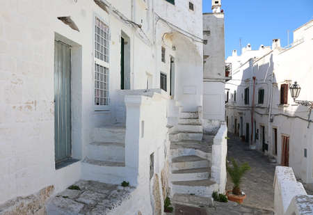 Typical narrow alleyway in an old white city of Ostuni in Apulia, Italy