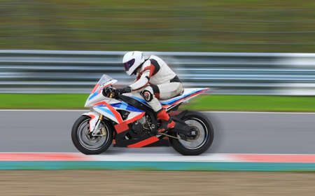 Motorcycle rider in a white helmet and gear racing at high speed on race track with motion blur