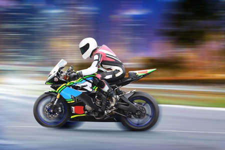 Motorcycle rider in a white helmet and gear racing at high speed on race track with motion blur. Sports theme