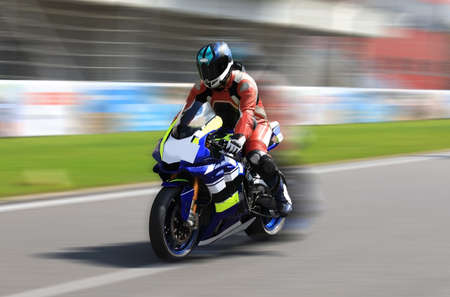 Racer on a sports bike rides on the race track at high speed with motion blur 免版税图像