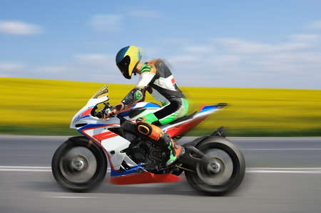 Racing bike rider racing outdoors at high speed with motion blur on a colorful background