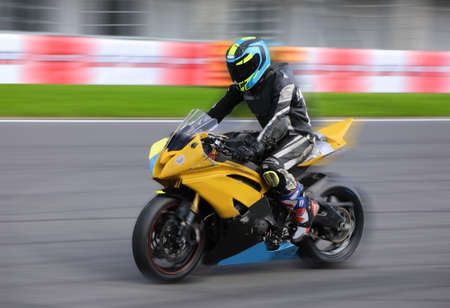 Motorcycle rider in a helmet and gear racing at high speed on race track with motion blur 스톡 콘텐츠