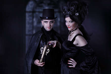 An insidious couple of vampires pour poison into a cup of wine inside of an old castle Imagens