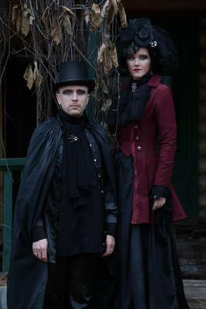 Giovane coppia sexy che indossa abiti in stile vampiro antiquato contro una vecchia villa Archivio Fotografico