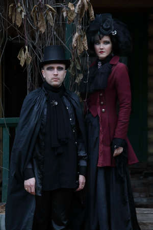 Sexy young couple wearing old-fashioned vampire-style clothes against an old mansion