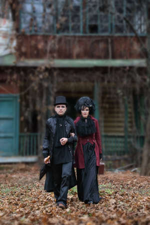 The sinister couple wearing old-fashioned vampire-style clothes walks through fallen foliage against the backdrop of an old mansion