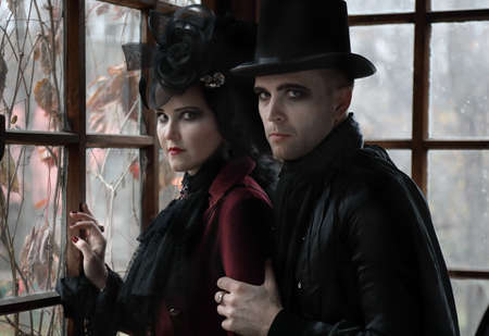 Portrait of a Lord of vampires with witch at the window of the old mansion