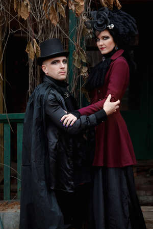 Portrait of a cute couple dressed in old fashioned clothes in vampire style on the porch of an old overgrown mansion
