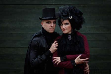 Attractive young couple dressed in old fashioned vampire style clothes against an old green wall Фото со стока