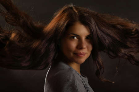 Portrait of a nice brunette girl with loose hair on a black background Foto de archivo - 133715308