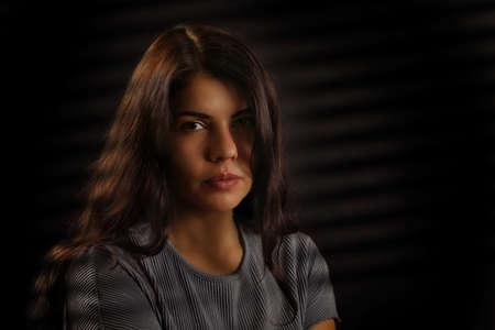 Portrait of a sad brunette girl on a black background Foto de archivo - 133715309