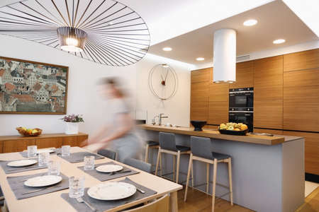 Interior of a kitchen and dining area with a girl setting the table in motion