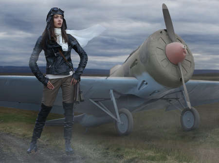 Beautiful girl pilot dressed in a retro pilot's uniform standing on the flying field next to a retro airplane in a light haze of evening fog Banco de Imagens