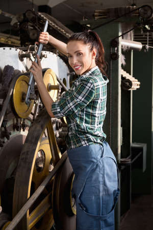 Beautiful brunette girl dressed in a plaid shirt and coverall repairs a spinning machine in the factory