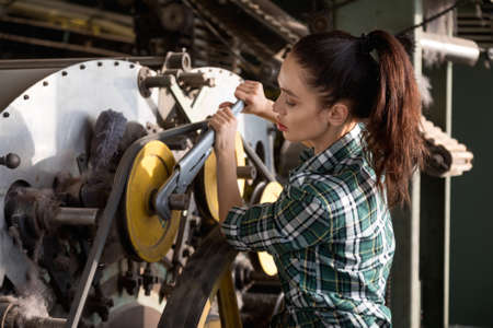 Pretty brunette girl dressed in a plaid shirt repairs a spinning machine with an adjustable wrench in a factory
