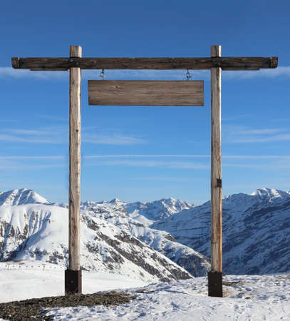 Wooden gate with a blank sign on top of a snow covered mountain. Mockup for adding roadmap text