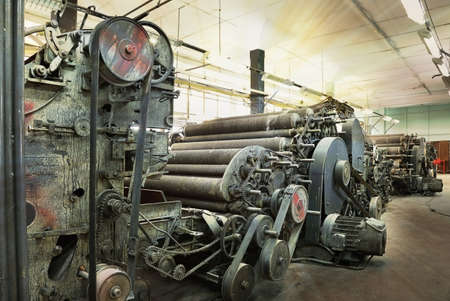 An old machine in the weaving shop at an abandoned textile factory in the morning sun
