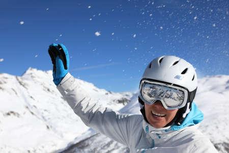 Porträt einer jungen Frau in Skianzug und Helm auf dem Hintergrund schneebedeckter Berge