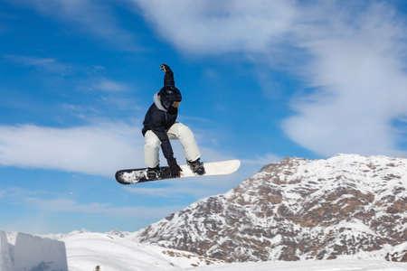 Le snowboarder saute dans le parc à neige dans les montagnes enneigées