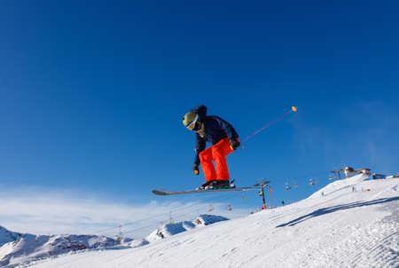 Skiër springt in het sneeuwpark in de besneeuwde bergen tegen de blauwe lucht in het skigebied Livigno, Italië Stockfoto