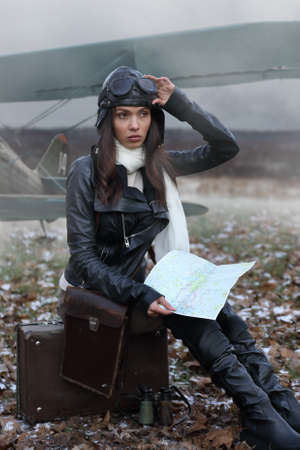 Beautiful young adult in a retro aviator costume looking at the map against the background of an old plane on the airfield