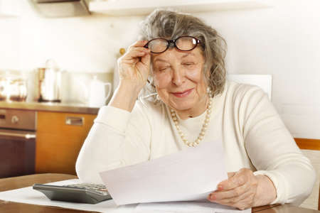 An old lady sitting at a table in the kitchen looking through receipts with a calculator