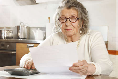 An old woman looks at bills and counts on a calculator sitting at a table in the kitchen