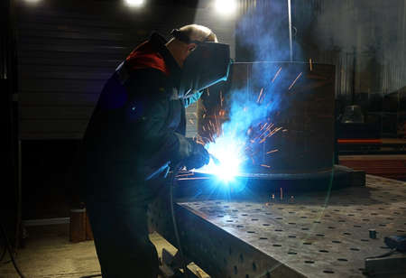 Metalworker in safety mask and gloves using welding torch to join sides of metal construction in the shop at the factory. Industrial theme