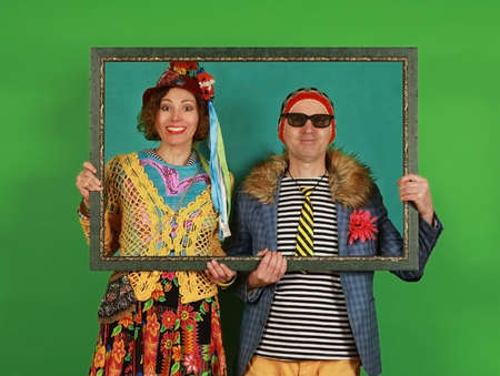 Funny freaky couple posing in the studio holding a picture frame in their hands on a green background