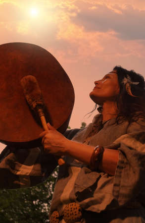 Female shaman performs a ritual with a tambourine at sunset in the forest. Shamanic ritual. Ethnic traditions