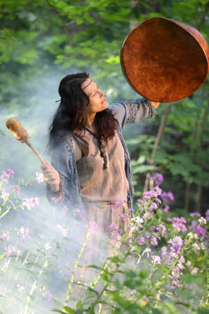 Shaman woman performs a ritual with a tambourine in the forest in the rays of the setting sun