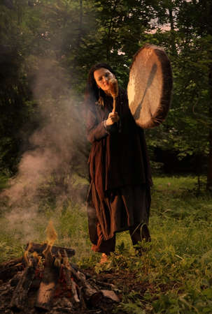 Shaman woman performs a ritual with a tambourine in the evening forest Stock Photo